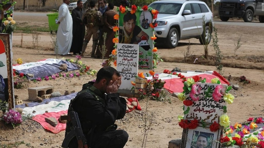 In this Wednesday, March 25, 2015, photo, a Sunni fighter from the al-Jabouri tribe weeps in front of the grave of his relative killed in a battle with Islamic State militants, as he visits a cemetery in the town of Duluiyah, 45 miles (75 kilometers) north of Baghdad, Iraq. Sunni tribes that have stood up to the IS group have paid a heavy price, and anger at the Shiite-led government runs deep in the areas of northern and western Iraq that now make up the extremist group's self-styled caliphate. (AP Photo/Karim Kadim)