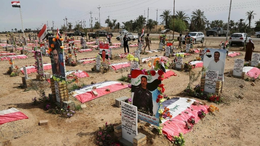 This Wednesday, March 25, 2015, photo shows a mass grave for al-Jabouri tribesmen, who were killed in battles against Islamic States militants, in the town of Duluiyah, 45 miles (75 kilometers) north of Baghdad, Iraq. Al-Jabouri Sunnis allied with Iraqi troops and Shiite militiamen took back the town from the Islamic State group in December. Sunni tribes that have stood up to the IS group have paid a heavy price, and anger at the Shiite-led government runs deep in the areas of northern and western Iraq that now make up the extremist group's self-styled caliphate. (AP Photo/Karim Kadim)