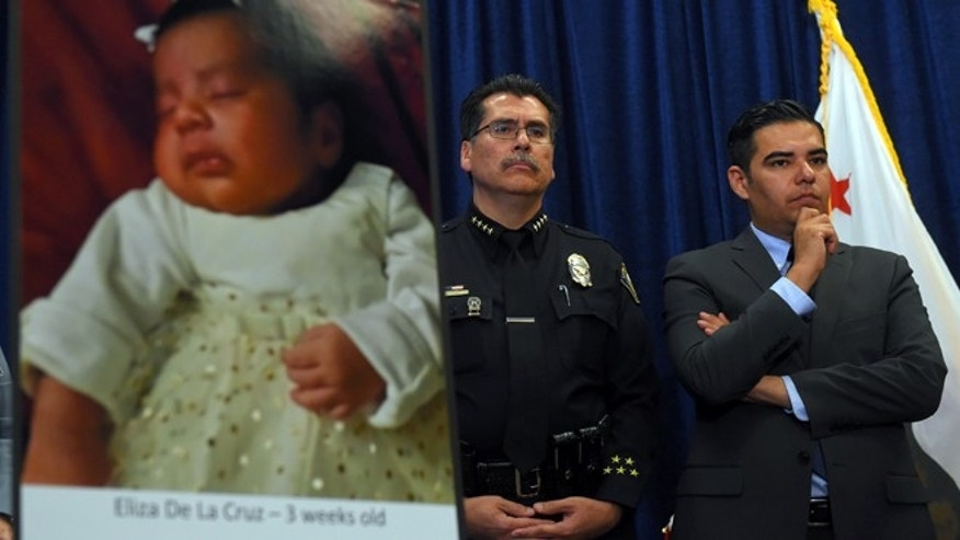 Long Beach Police Chief Robert Luna, left, and Mayor Robert Garcia stand during a news conference in Long Beach, Calif., Wednesday, March 25, 2015. Southern California authorities have arrested four people in a plot to kidnap two newborn babies. The plot ended with the death of a 3-week-old girl and the shooting and beating of the childrenâs mothers, police said Wednesday. At left is an image of baby Eliza Delacruz, who was snatched Jan. 3, 2015, in Long Beach by a gunman who wounded her parents and uncle, Luna said. Her body was found the next day in a trash bin near the Mexican border. (AP Photo/The Daily Breeze, Scott Varley)  MAGS OUT; NO SALES