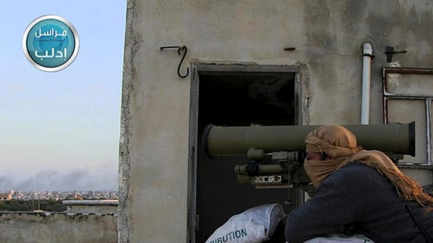 In this image posted on the Twitter page of Syria's al-Qaida-linked Nusra Front on Friday, March 27, 2015, which is consistent with AP reporting, a fighter from Syria's al-Qaida-linked Nusra Front takes his position as he fights against the Syrian government forces in Idlib province, north Syria. Al-Qaida's affiliate in Syria, the Nusra Front, captured most of the northwestern city of Idlib from government forces Saturday, sweeping into neighborhoods in the center of the city in a powerful blow to President Bashar Assad's government, opposition activists and the group said. (AP Photo/Nusra Front on Twitter)