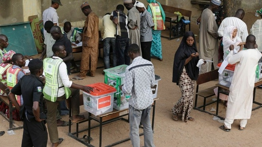 Mar. 28, 2015: A police officer stand guards as people cast their votes during Presidential and National assembly election in Yola, Nigeria. (AP)