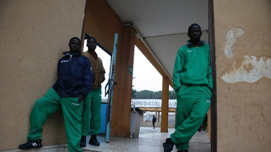 "In this picture taken Tuesday, March 24, 2015 and made available Saturday, March 28, 2015, migrants stand in front of the entrance of the ""Umberto I"" migrant holding center in Siracusa, Sicily, Italy. The U.N. refugee agency reported that the number of asylum requests rose 148 percent in 2014 over the previous year, far surpassing its previous all-time high in 2011 some 40,000 people sought refugee status in Italy during the Arab Spring. (AP Photo/Luca Bruno)"