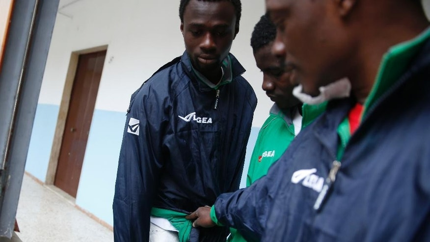 "In this picture taken Tuesday, March 24, 2015 and made available Saturday, March 28, 2015 Ismail Konate', left, a 23-year-old from Ivory Coast who traveled to Italy aboard a life raft, shows his wounds caused by fuel to the photographer at the ""Umberto I"" migrant holding center in Siracusa, Sicily, Italy. The U.N. refugee agency reported that the number of asylum requests rose 148 percent in 2014 over the previous year, far surpassing its previous all-time high in 2011 some 40,000 people sought refugee status in Italy during the Arab Spring. (AP Photo/Luca Bruno)"