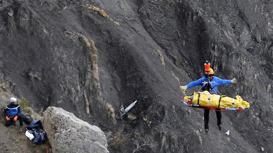 FILE - In this Thursday March 26, 2015 file photo a rescue worker is lifted into an helicopter at the crash site near near Seyne-les-Alpes, France. The somber mission to recover the remains of 150 people killed instantly when the Germanwings flight slammed full speed into the Col de Mariaud is not a quiet one and crucial physical evidence for the crash investigation can be gathered only when the mountains cooperate. (AP Photo/Laurent Cipriani, File)