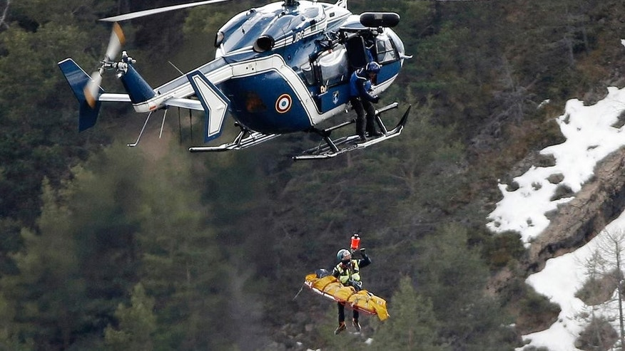FILE - In this Thursday March 26, 2015 file photo a rescue worker is lifted into a helicopter at the crash site near near Seyne-les-Alpes, France. The somber mission to recover the remains of 150 people killed instantly when the Germanwings flight slammed full speed into the Col de Mariaud is not a quiet one and crucial physical evidence for the crash investigation can be gathered only when the mountains cooperate. (AP Photo/Laurent Cipriani, File)