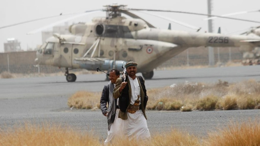 "Shiite rebels, known as Houthis, walk on the tarmac of the Sanaa International Airport in Sanaa, Yemen, Saturday, March 28, 2015. Yemen's President Abed Raboo Mansour Hadi, speaking at the opening session of an Arab summit in Egypt on Saturday, called Shiite rebels who forced him to flee the country ""stooges of Iran,"" directly blaming the Islamic Republic for the chaos there and demanding airstrikes against rebel positions continue until they surrender. (AP Photo/Hani Mohammed)"