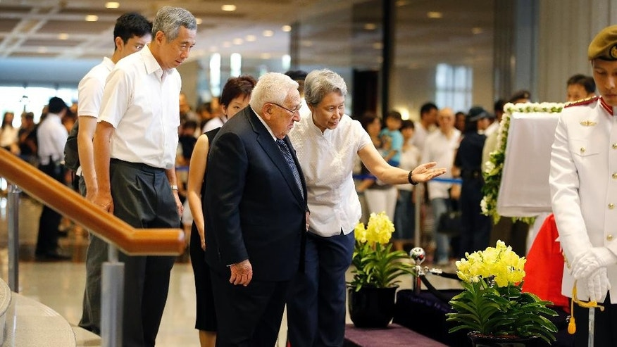Former U.S. Secretary of State Henry Kissinger, center, is accompanied by Ho Ching, right, wife of Singapore's Prime Minister Lee Hsien Loong, second left, as he pays his respects  to the late Lee Kuan Yew, Saturday, March 28, 2015, in Singapore. Lee, 91, died Monday at Singapore General Hospital after more than a month of battling severe pneumonia. The government declared a week of mourning for the leader who is credited with transforming the resource-poor island into a wealthy finance and trade hub with low crime and corruption in a region saddled with graft, instability and poverty. (AP Photo/Wong Maye-E)