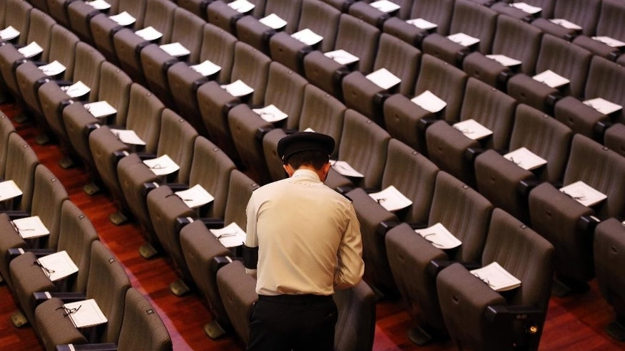 An army officer arranges funeral service programs on seats ahead of a state funeral for the late Lee Kuan Yew, at the University Cultural Center, Sunday, March 29, 2015, in Singapore. During a week of national mourning that began Monday after Lee's death at age 91, some 450,000 people queued for hours for a glimpse of Lee's coffin at Parliament House. A million people visited tribute sites at community centers across the island and leaders and dignitaries from more than two dozen countries attended the state funeral. (AP Photo/Wong Maye-E)