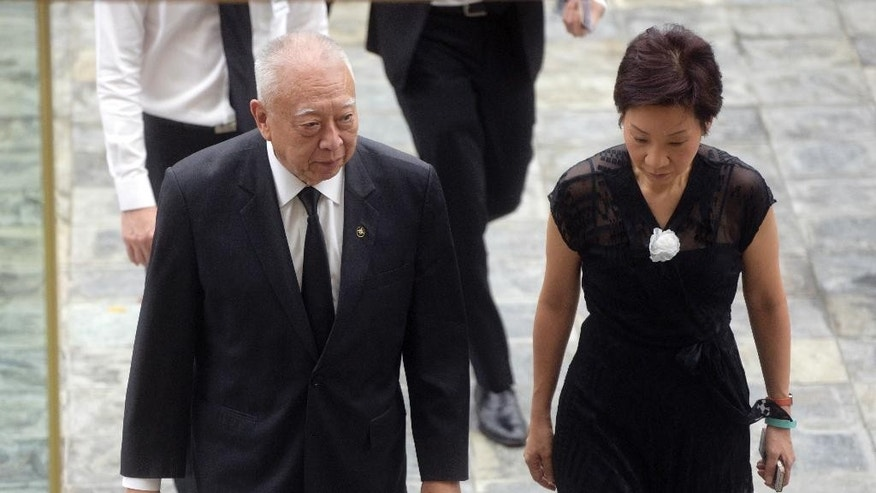 Former Hong Kong Chief Executive Tung Chee-hwa, left, is welcomed  by Singapore Minister of the Prime Minister's Office Grace Fu, right, as he arrives at the state funeral for the late Lee Kuan Yew, at the University Cultural Center Sunday, March 29, 2015 in Singapore. Thousands of Singaporeans are lining a 15 kilometer (9 mile) route through the Southeast Asian city-state to witness an elaborate funeral procession Sunday for longtime leader Lee Kuan Yew. (AP Photo/Joseph Nair)