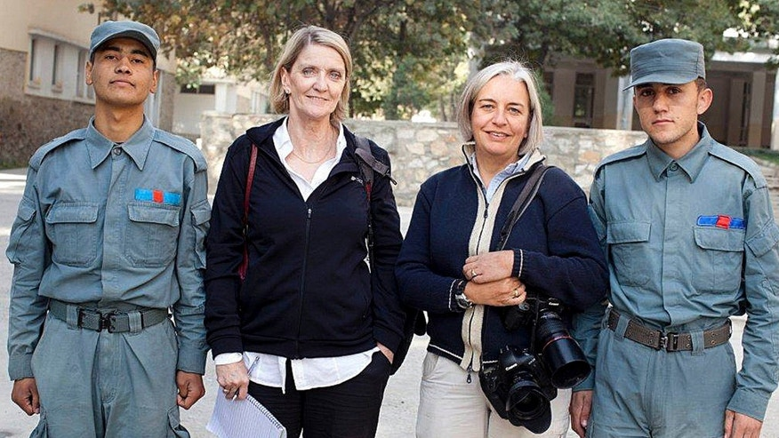In this photo taken in October 2012, Associated Press reporter Kathy Gannon, second from left, and photographer Anja Niedringhaus pose for a photo with Afghan police recruits at the main police training academy in Kabul, Afghanistan.
