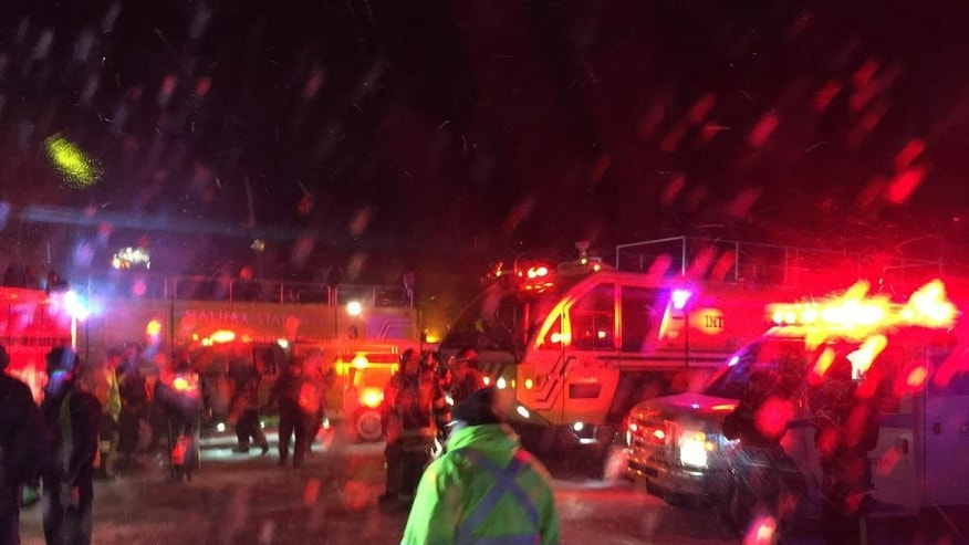 Fire trucks and an airport shuttle are on the scene at the Halifax International Airport early Sunday March 29, 2015 after an Air Canada flight from Toronto made an abrupt landing and left the runway in bad weather. The airline said early Sunday that 22 people were taken to a hospital for observation and treatment of minor injuries.  (AP Photo/Mike Magnus)