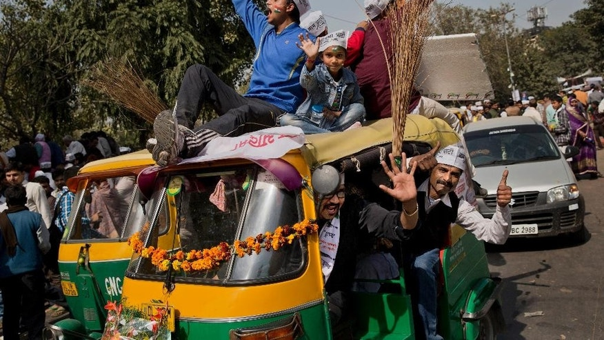 FILE- In this, Feb. 14, 2015 file photo, supporters of the Aam Aadmi Party (AAP), or Common Man's Party, shout slogans as they sit on an autorickshaw decorated with brooms, the party symbol, outside the venue where party leader Arvind Kejriwal is being sworn-in as the new chief minister of Delhi, in New Delhi, India. The upstart AAP, was once seen by many as a breath of fresh air in the chaotic, corruption-tainted world of Indian politics, promising to root out graft and display complete transparency. Now, however, with its top leaders spending the weekend slugging it out in public, it seems the party that promised to transform India's political landscape is more likely to bring disappointment to millions of Indians despairing of their politicians.. (AP Photo/Bernat Armangue, file)