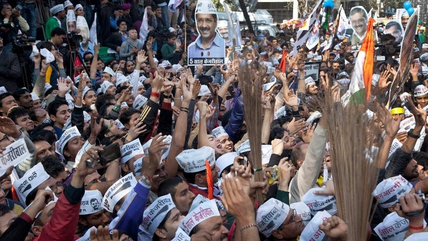 FILE- In this Feb. 10, 2015 file photo, supporters of the Aam Aadmi Party (AAP), or Common Man's Party, hold cut-outs of their leader Arvind Kejriwal and their party symbol, the broom, as they celebrate the party's victory in New Delhi, India. The upstart AAP, was once seen by many as a breath of fresh air in the chaotic, corruption-tainted world of Indian politics, promising to root out graft and display complete transparency. Now, however, with its top leaders spending the weekend slugging it out in public, it seems the party that promised to transform India's political landscape is more likely to bring disappointment to millions of Indians despairing of their politicians.(AP Photo/Tsering Topgyal, file)