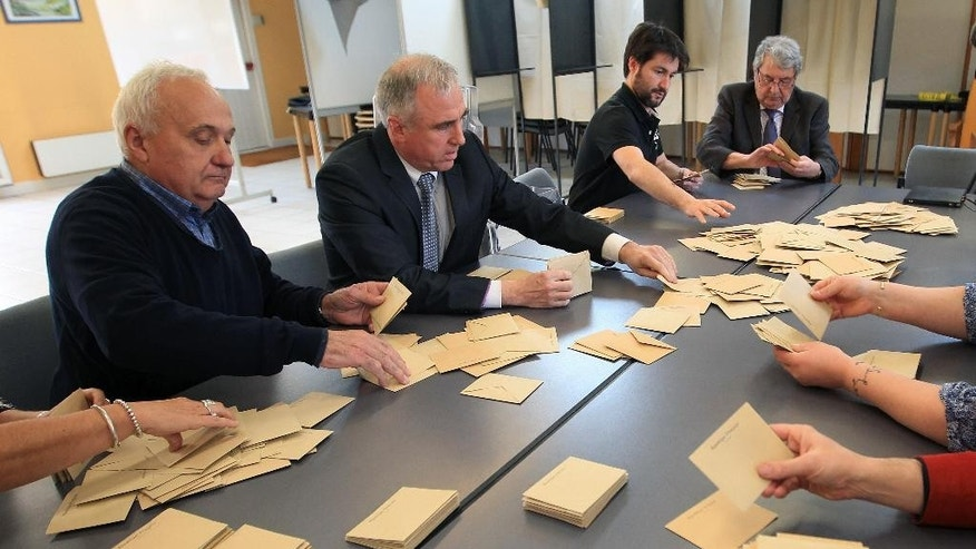 Councilors strip ballot papers during the second round of local elections, Sunday, March 29, 2015, in Saint Pierre d'Irube, southwestern France. For president of Front National Marie Le Pen, today's election for more than 2,000 local councils is an important step in building a grassroots base critical to her ultimate goal: the 2017 presidency. (AP Photo/Bob Edme)