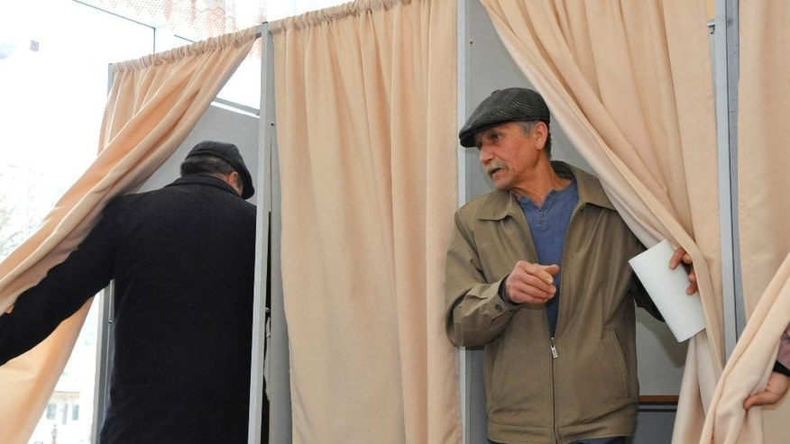 Uzbek citizens leave voting cabins at a polling station in Tashkent, Uzbekistan, Sunday, March 29, 2015. Islam Karimov, 77, has led the double-landlocked former Soviet republic of 30 million people uninterruptedly since the late 1980s, and ruthlessly quashed all opposition to his rule. Uzbekistan's election commission says more than 70 percent of eligible voters have already cast their ballots midway through an election certain to be won by longtime leader Islam Karimov. (AP Photo)