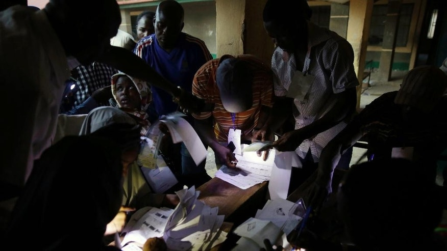 Election officials  use the lights from their cellphones to prepare ballots for late voters in one of the polling stations  in Kaduna,  Nigeria,  Saturday, March 28, 2015. A Nigerian official says voting is being extended to Sunday in areas that have experienced problems in checking voters' identities. (AP Photo/Jerome Delay)