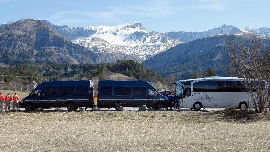 Buses of the French gendarmerie, park and mask the homage ceremony with family members of Japanese victims in the area where the Germanwings jetliner crashed in the French Alps, in Le Vernet, France, Sunday, March 29, 2015. The crash of Germanwings Flight 9525 into an Alpine mountain Tuesday killed all 150 people aboard, and has raised questions about the mental state of the co-pilot. Authorities believe the 27-year-old German deliberately sought to destroy the Airbus A320 as it flew from Barcelona to Duesseldorf. (AP Photo/Claude Paris)