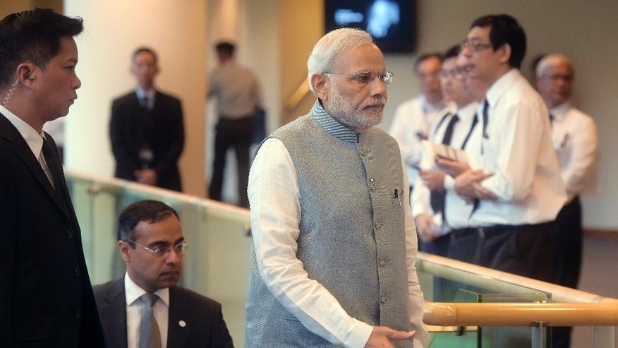 India's Prime Minister Narendra Modi, center, arrives at the state funeral for the late Lee Kuan Yew, at the University Cultural Center,  Sunday, March 29, 2015 in Singapore. During a week of national mourning that began Monday after Lee's death at age 91, some 450,000 people queued for hours for a glimpse of Lee's coffin at Parliament House. A million people visited tribute sites at community centers across the island and leaders and dignitaries from more than two dozen countries attended the state funeral. (AP Photo/Joseph Nair)
