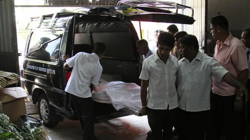 In this Saturday, March 28, 2015 photo, Sri Lankan workers carry the body of the Priyantha Sirisena, Sri Lankan President Maithripala Sirisena's youngest brother, to a funeral parlor in Colombo, Sri Lanka. Sirisena, 42, died in a private hospital in Colombo on Saturday after he was attacked with an axe in what authorities said was a personal dispute. Unlike his predecessor Mahinda Rajapaksa, whose brothers and other family members held top government positions, Sirisena has kept his family out of politics and has not given them state protection. (AP Photo/Eranga Jayawardena)