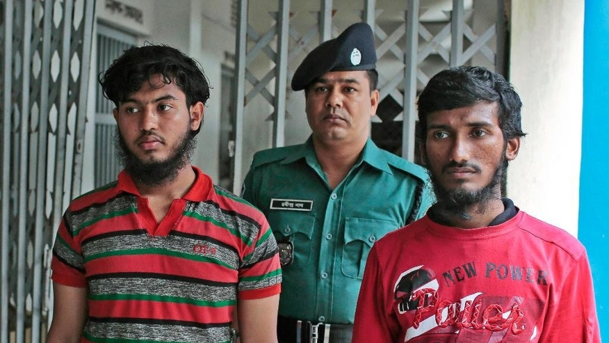 A Bangladeshi policeman escorts Jikrullah, left and Ariful Islam, two among  three suspected of the killing of a blogger as they are presented before the media in Dhaka, Bangladesh, Monday, March 30, 2015. Blogger Washiqur Rahman Babu, 26, was hacked to death by three men in Bangladesh's capital on Monday, police said. The killing took place a month after a prominent Bangladeshi-American blogger known for speaking out against religious extremism was hacked to death in Dhaka. (AP Photo/ A.M. Ahad)