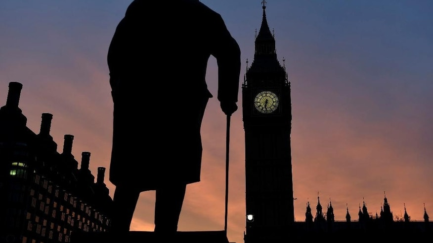 The sun rises behind the Palace of Westminster and the statue of Sir Winston Churchill in central London Monday March 30, 2015. Britain's Prime Minister David Cameron will visit the Queen Elizabeth II on Monday for a final audience ahead of the May 7 General Election formally marking the end of the five-year coalition government.  (AP Photo/PA, Andrew Matthews)  UNITED KINGDOM OUT: NO SALES: NO ARCHIVE