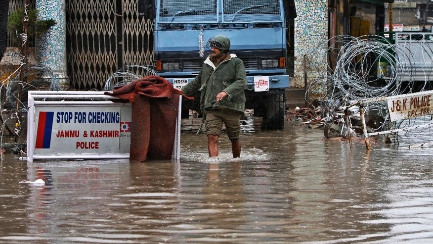 An Indian paramilitary soldier walks through a flooded street following heavy rains in Srinagar, Indian controlled Kashmir, Sunday, March 29, 2015. Heavy rains have been reported in several parts of the Kashmir valley. (AP Photo/Mukhtar Khan)