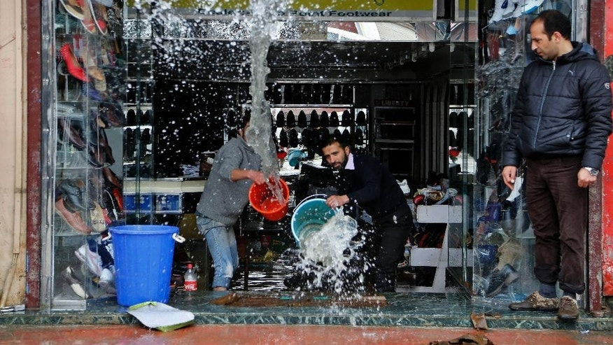 Kashmiri shopkeepers try to remove water from inside a footwear shop following heavy rains in Srinagar, Indian controlled Kashmir, Sunday, March 29, 2015. Heavy rains have been reported in several parts of the Kashmir valley. (AP Photo/Mukhtar Khan)