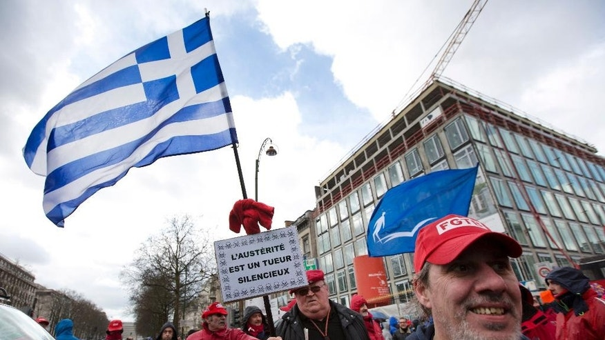"A trade unionist holds a Greek flag and a sign which reads ""austerity is a silent killer"", during a demonstration against Belgian austerity reforms in Brussels on Monday, March 30, 2015. Like a series of strike actions late last year, the protesters targeted measures by the business-friendly government of Prime Minister Charles Michel to cut into employees' income, extend working time and restrict social services. (AP Photo/Virginia Mayo)"