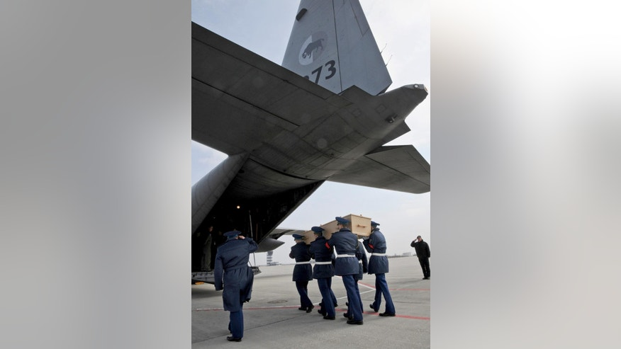 A Ukrainian honor guard carry a coffin with the remains of a victim of Malaysia Airlines flight 17 which was brought down over conflict-torn eastern Ukraine on July 17, 2014, into an aircraft headed to the Netherlands, in the city airport of Kharkiv, Ukraine, Saturday, March 28, 2015. The plane was brought down by a surface-to-air missile last July over pro-Russian rebel-held territory in eastern Ukraine, killing all 298 passengers and crew on board. (AP Photo)
