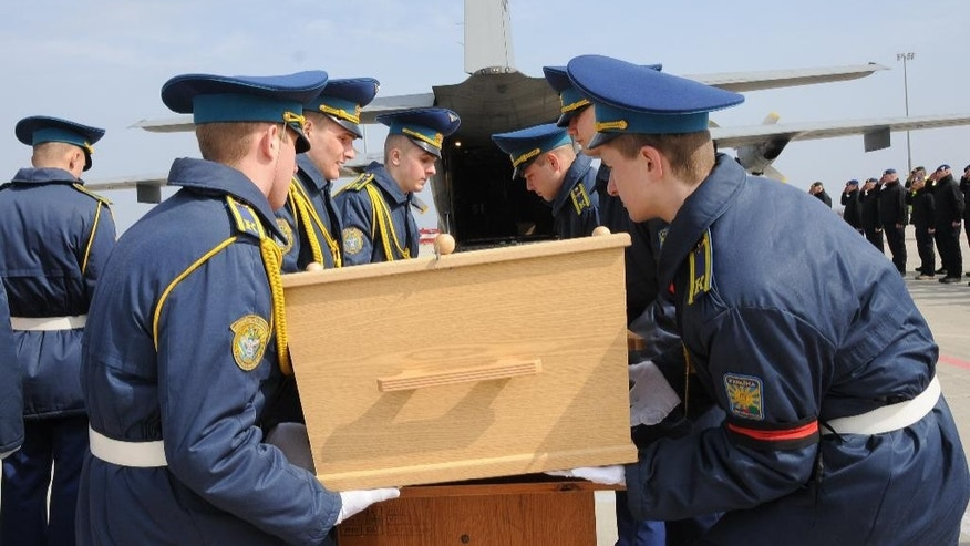 A Ukrainian honor guard lift a coffin with the remains of a victim of Malaysia Airlines flight 17 which was brought down over conflict-torn eastern Ukraine on July 17, 2014, to take it into an aircraft headed to the Netherlands, in the city airport of Kharkiv, Ukraine, Saturday, March 28, 2015. The plane was brought down by a surface-to-air missile last July over pro-Russian rebel-held territory in eastern Ukraine, killing all 298 passengers and crew on board. (AP Photo)