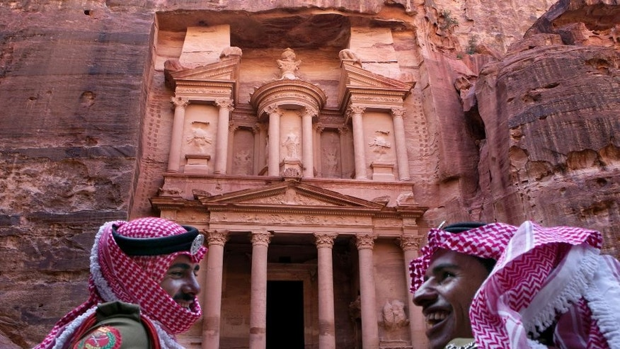 "In this Tuesday, March 24, 2015 photo, Jordanian royal desert forces stand guard in front of Al Khazneh, Arabic for the Treasury, the most dramatic of many facades carved into the mountains, in the ancient city of Petra, Jordan. It's high season in Petra, the ancient city hewn from rose-colored rock and Jordan's biggest tourist draw. Yet nearby hotels stand virtually empty these days and only a trickle of tourists make their way through a landmark canyon to the Treasury building where scenes of one of the ""Indiana Jones"" movies were filmed. (AP Photo/Raad Adayleh)"