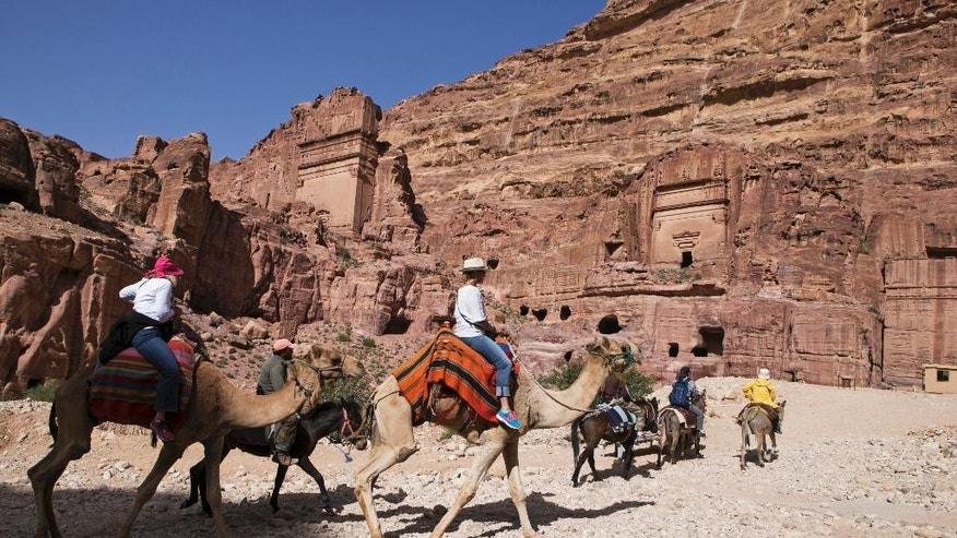 In this Tuesday, March 24, 2015 photo, tourists ride around the ancient city of Petra, Jordan. In Petra, a UNESCO World Heritage site, the number of annual visitors dropped from 800,000 in 2010 to 400,000 last year, said Yassar al-Majali, general manager of the Jordan Hotel Association. (AP Photo/Raad Adayleh)