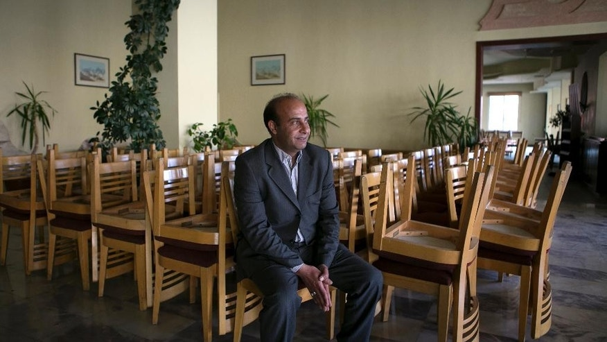 "In this Tuesday, March 24, 2015 photo, Ahmad Amarat, manager of the Kings' Way Hotel, speaks during an interview with The Associated Press in the ancient city of Petra, Jordan. ""We are not optimistic for 2015,"" Amarat said. The hotel closed four months ago after an average occupancy rate of 28 percent for 2014, compared to 95 percent in 2010. (AP Photo/Raad Adayleh)"