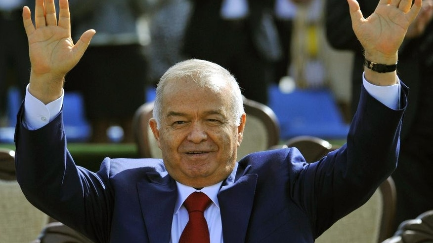 FILE - In this Saturday, March  21, 2015 file photo, Uzbekistan's President Islam Karimov greets people during the festivities marking the Navruz holiday in Tashkent, Uzbekistan. Uzbekistan's election commission said more than 70 percent of eligible voters had cast their ballots by midway through Sunday's presidential election, where victory by longtime leader Islam Karimov is a foregone conclusion. (AP Photo/File)