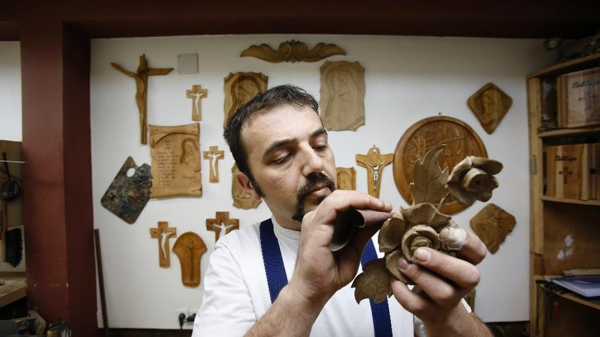 In this photo taken on Saturday, March, 28,2015 Bosnian Muslim craftsman  Edin Hajdarovac engraves decoration onto part a wooden chair in his workshop in Bosnian town of Zavidovici, 170 kms north of Sarajevo.  Salem Hajdarovac didn't sleep for a whole week when he heard his workshop had been granted the honor of carving a special chair that Pope Francis will sit on during his visit to Bosnia.  Hajdarovac and his son Edin, both devote Muslims, started working on the chair on Monday March 30, 2015 in their little workshop in the central Bosnian town of Zavidovici.(AP Photo/Amel Emric)