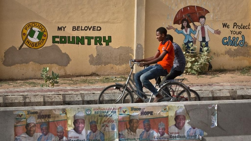 Two youths ride bicycles past a mural on a school wall and election posters supporting President Goodluck Jonathan, on a street in Kano, Nigeria Sunday, March 29, 2015. Voting in Nigeria's elections continued in certain areas on Sunday after technical problems prevented some people from casting their ballots on Saturday and despite extremist violence in the northeast and protests in the south. (AP Photo/Ben Curtis)