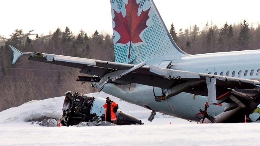 An investigator inspects an Air Canada flight plane that landed hard and skidded off the runway in the midst of a snowstorm at Stanfield International Airport in Halifax, Nova Scotia, Sunday, March 29, 2015. Chief operating officer Klaus Goersch said 25 people were taken to hospital and all but one of them were released. (AP Photo/The Canadian Press, Andrew Vaughan)