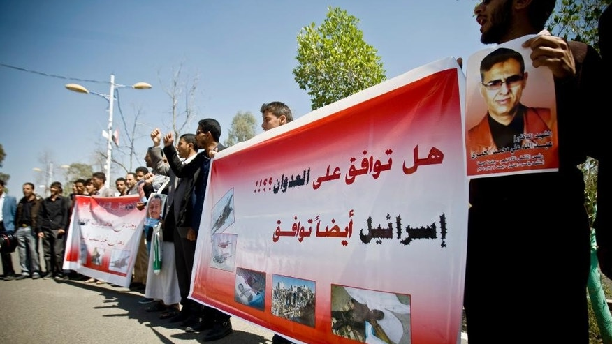 "Yemenis gather during a rally against Saudi-led airstrikes on Shiite rebels, known as Houthis, in Sanaa, Yemen, Monday, March 30, 2015. Arabic writing on a banner reads, ""Do you agree on the attack? Israel also agrees.""(AP Photo/Hani Mohammed)"