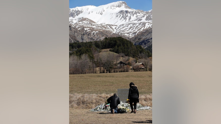 Family members of a victim kneel by a stele and flowers laid in memory of the victims are placed in the area where the Germanwings jetliner crashed in the French Alps, in Le Vernet, France, Friday, March 27, 2015. The crash of Germanwings Flight 9525 into an Alpine mountain, which killed all 150 people aboard, has raised questions about the mental state of the co-pilot. Authorities believe the 27-year-old German deliberately sought to destroy the Airbus A320 as it flew Tuesday from Barcelona to Duesseldorf. (AP Photo/Christophe Ena)