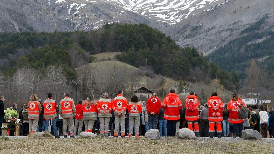 French Red Cross members and inhabitants pay tribute to the victims in front of a stele, a stone slab erected as a monument, set up in the area where a Germanwings aircraft crashed in the French Alps, in Le Vernet, France, Saturday, March 28, 2015. The crash of Germanwings Flight 9525 into an Alpine mountain Tuesday killed all 150 people aboard, and has raised questions about the mental state of the co-pilot. Authorities believe the 27-year-old German deliberately sought to destroy the Airbus A320 as it flew from Barcelona to Duesseldorf. (AP Photo/Claude Paris)
