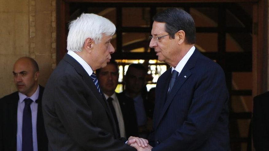 Cyprus' President Nicos Anastasiades, right, and President of Greece, Prokopis Pavlopoulos, talk as they shake hands after their meeting at the presidential palace in the capital Nicosia, Cyprus, Monday, March 30, 2015. President of Greece Prokopis Pavlopoulos arrived in Cyprus for a two-day official visit, his first since assuming his duties. (AP Photo/Petros Karadjias)
