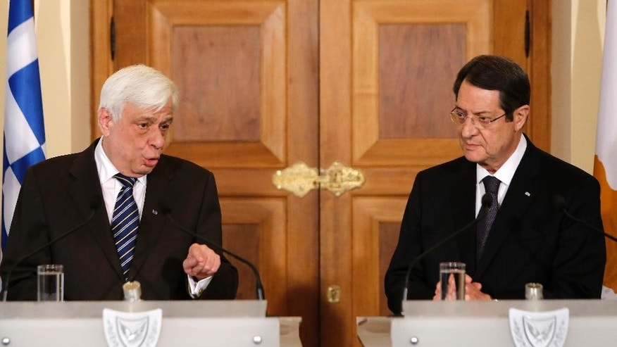 Cyprus' President Nicos Anastasiades, right and President of Greece, Prokopis Pavlopoulos, speak to the media during a press conference after their meeting at the presidential palace in the capital Nicosia, Cyprus, Monday, March 30 , 2015. President of Greece Prokopis Pavlopoulos arrived in Cyprus for a two-day official visit, his first since assuming his duties. (AP Photo/Petros Karadjias)