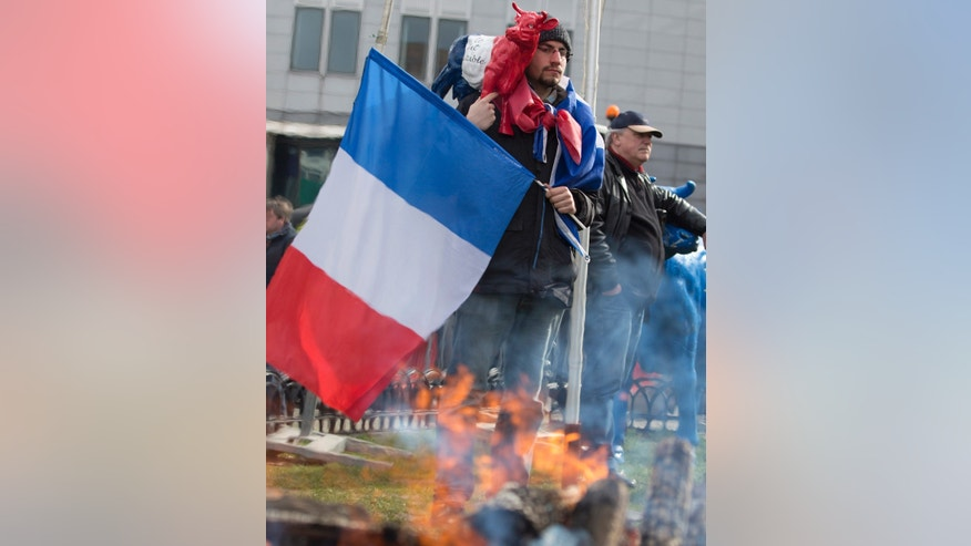 Tuesday, March 31, 2015: A farmer holds a French flag and a plastic cow during a demonstration against the lifting of milk quotas in front of the European Parliament in Brussels.