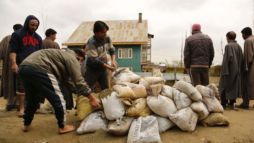 Kashmiris carry sand bags to repair breach in an embankment in a flooded area following three days of incessant rain in Srinagar, Indian controlled Kashmir, Tuesday, March 31, 2015. Although flood waters were receding, residents in the main city of Srinagar were bracing for more trouble as the meteorological office has predicted more rain over the next few days. (AP Photo/Mukhtar Khan)