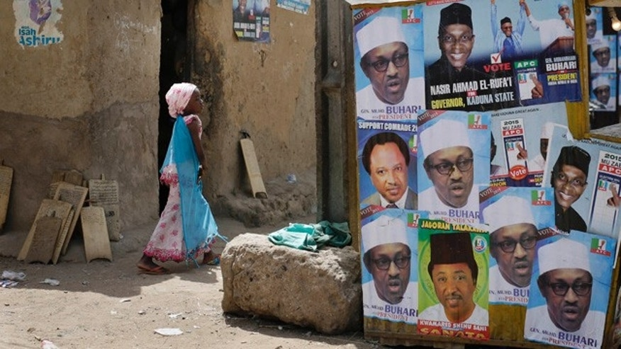 March 30, 2015: A young Nigerian girl walks past election posters, some showing presidential candidate, Muhammadu Buhari, in Kaduna, Nigeria. (AP Photo/Jerome Delay)