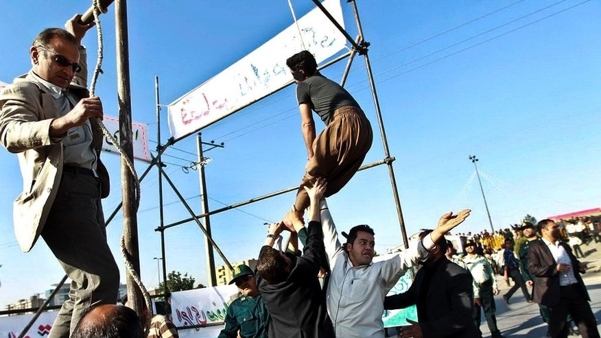 FILE - In this May 8, 2013, file photo released by the Iranian Mehr News Agency, men hold a man hanged in public, to prevent his execution, after he was pardoned by the family of the policeman he was convicted of killing, in Mashhad, northeastern Iran. Under Sharia law, a victim's family has the option to forgive the criminal rather than allowing the perpetrator to be executed. According to a report by Amnesty International released on Wednesday, April 1, 2015, Iran had at least 289 recorded executions in 2014. (AP Photo/Mehdi Bolourian)
