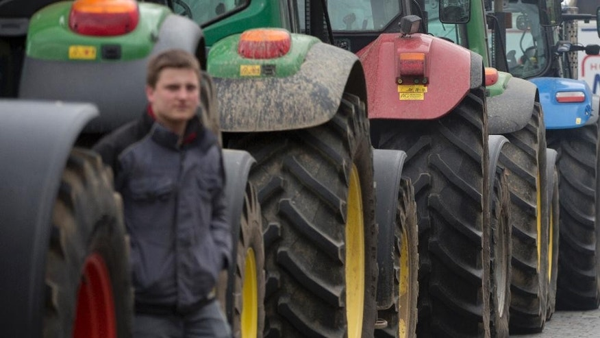 A farmer walks next to the tractors of dairy farmers during a demonstration against the lifting of milk quotas in front of the European Parliament in Brussels on Tuesday, March 31, 2015. Dairy farmers hit the streets of Brussels to protest against the lifting European Union milk quotas amid concern the move will flood the market with surplus milk. (AP Photo/Virginia Mayo)
