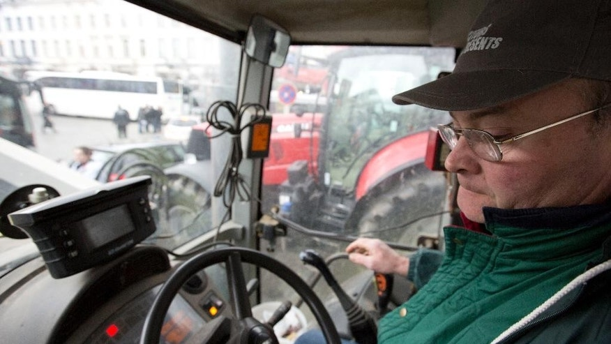 Belgian Dairy farmer Yvan Deknudt drives his tractor during a demonstration against the lifting of milk quotas in front of the European Parliament in Brussels on Tuesday, March 31, 2015. Dairy farmers hit the streets of Brussels to protest against the lifting European Union milk quotas amid concern the move will flood the market with surplus milk. (AP Photo/Virginia Mayo)