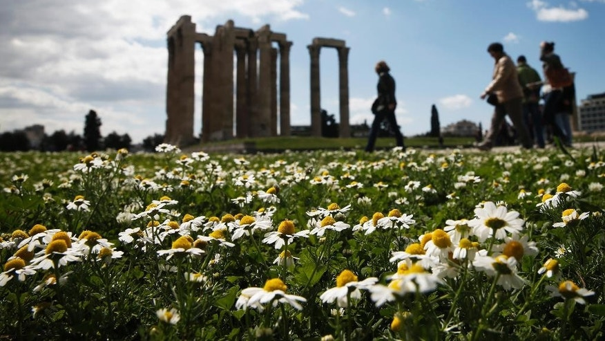 Tourist walk among flowers and the ancient Temple of Zeus in Athens, on Tuesday, March 31, 2015.  Tourism industry officials expected arrivals to reach 25 million this year, up by one million from 2014.  (AP Photo/Petros Giannakouris)