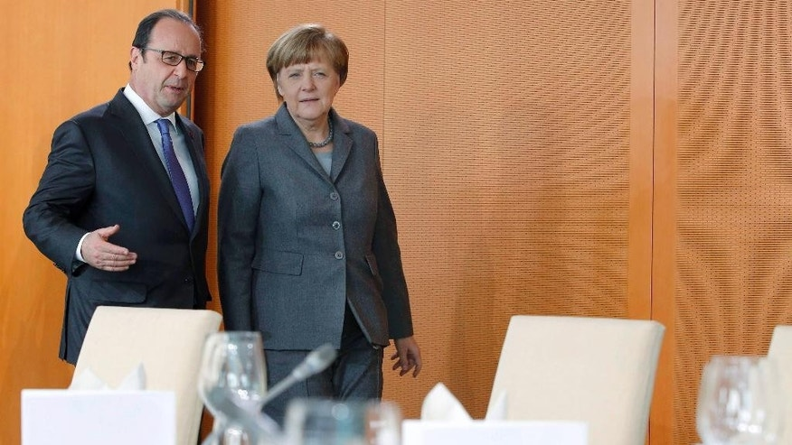 French President Francois Hollande, left, speaks to German Chancellor Angela Merkel as they arrive for a working lunch with their delegations in Berlin, Germany, Tuesday, March 31, 2015. (AP Photo/Fabrizio Bensch, Pool)